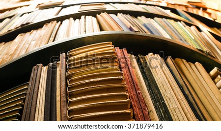 Many books on bookshelf in library, image with perspective distortion - stock photo