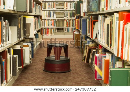 Many books on the bookshelves at a public library. - stock photo