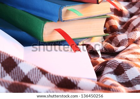 Many books with bookmarks on plaid close-up - stock photo
