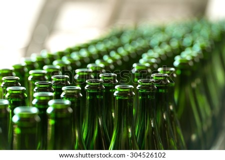 Many bottles on conveyor belt in factory - stock photo
