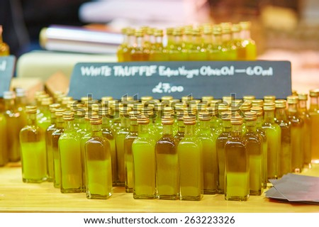 Many bottles with fresh organic extra virgin olive oil with truffles on London farmer agricultural market - stock photo