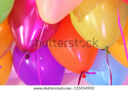 Many bright balloons under ceiling close-up - stock photo