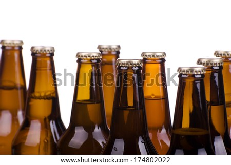 Many brown glass dark bottles full of beer on white, fresh drink in transparent glass. Object in horizontal orientation, nobody in frame. - stock photo