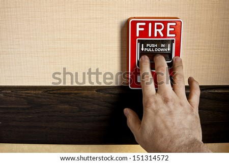 Many buildings have manual fire alarm boxes. A man's hand is on the alarm lever to activate it. There is room for your copy on the left side. - stock photo