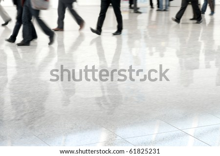 Many business people in blurred motion in a fair hall - stock photo