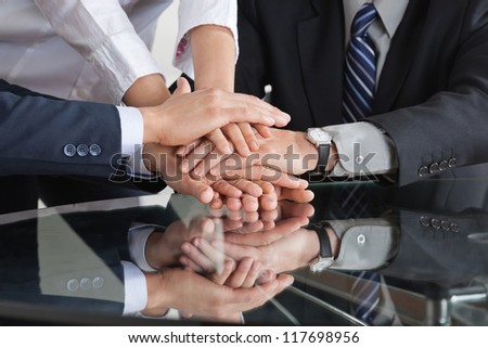 Many business people stacking hands to a pile - stock photo