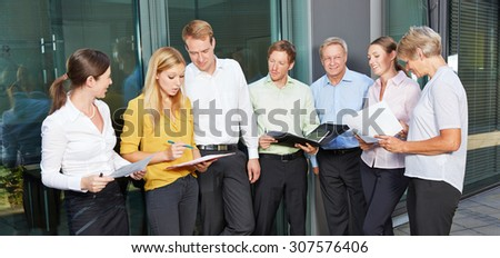 Many business people standing outside the office and talking to each other