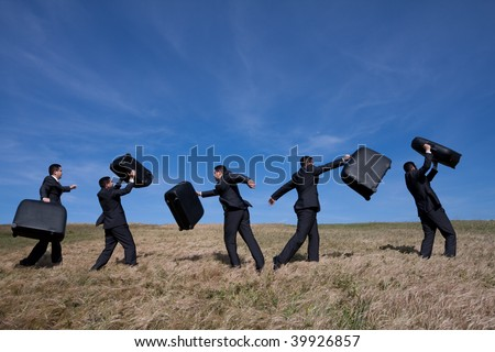 many businessman in the field walking with his luggage - stock photo