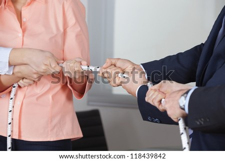 Many businesspeople playing tug of war in the office - stock photo