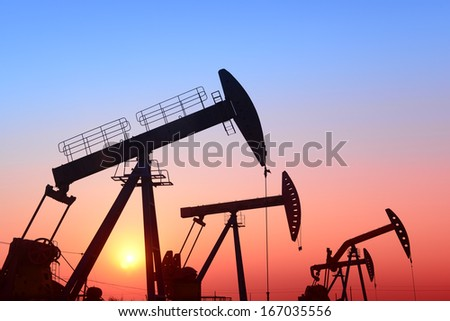 Many busy pumping unit under the setting sun   - stock photo