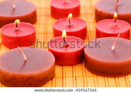 Many candles on bamboo mat background.