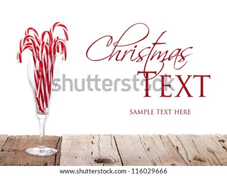 Many Candy canes in a wine glass on a wooden plank with an isolated white background - stock photo