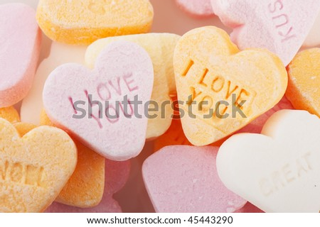 Many candy hearts with text and love you - stock photo
