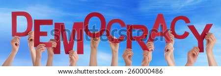 Many Caucasian People And Hands Holding Red Letters Or Characters Building The English Word Democracy On Blue Sky - stock photo