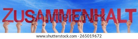 Many Caucasian People And Hands Holding Red Straight Letters Or Characters Building The German Word Zusammenhalt Which Means Solidarity On Blue Sky - stock photo