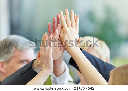 Many cheering hands giving High Five in the business office - stock photo