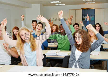 Many cheering students with hands raised in university class