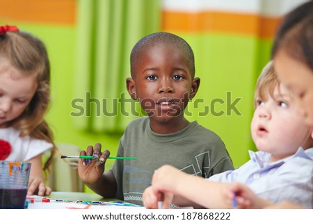 Many children in preschool painting together with brushes and color - stock photo