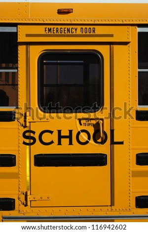 Many children rely on the iconic yellow school bus for transportation; closeup of emergency door. - stock photo