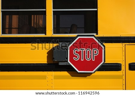 Many children rely on the iconic yellow school bus for transportation; detail of stop sign. - stock photo