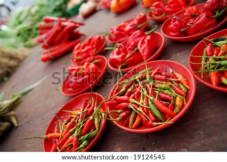 Many chilly peppers on red plates
