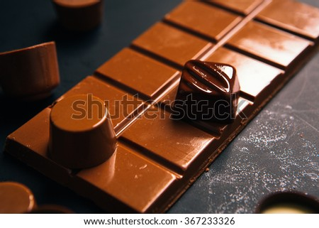 Many chocolate  candy sweets  on black background  - stock photo