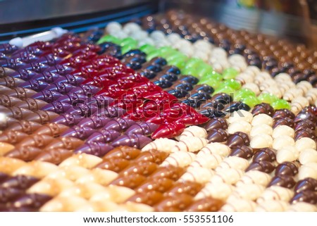 Many chocolates handmade in the window of a candy store. Multi-colored chocolate products, beautiful and delicious.