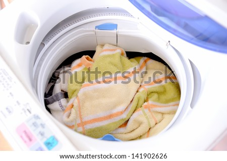 many clothes in washing machine - stock photo