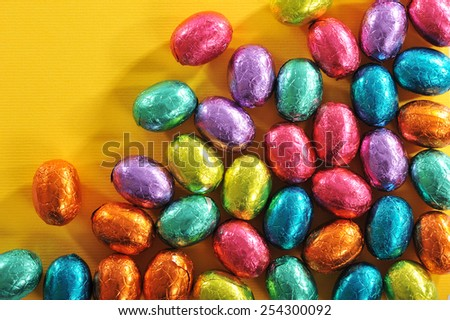 Many colored chocolate easter eggs on yellow paper - stock photo