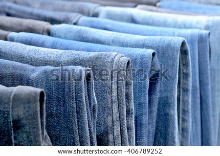 Many colored jeans hanging on hangers. - stock photo