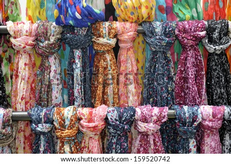 Many colored scarves on a display rack - stock photo