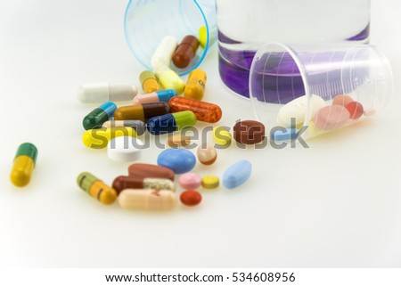Many colored tablets and capsules near a glass of water with purple bottom isolated on white background.