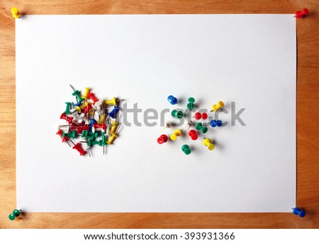 Many colored thumbtacks stuck into a white sheet of paper. A sheet of paper attached to a wooden board office - stock photo