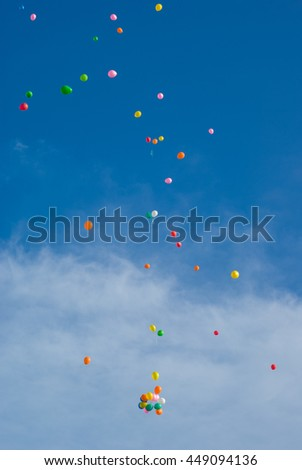 Many colorful balloons floating in sky background - stock photo