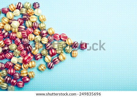 many colorful candies over aquamarine background with copy space - stock photo