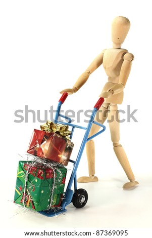 many colorful Christmas presents on a hand truck with wooden figure - stock photo