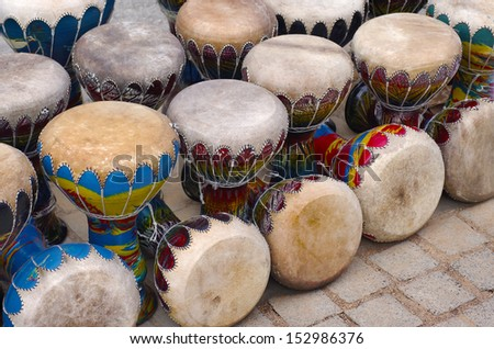Many colorful congas or hand-drums for sale in a handicraft market - stock photo