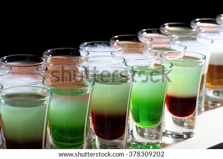 Many colorful green red white delicious sweet shooters cocktail alcoholic liquid in beautiful drinking glasses standing in line on bar night club party on black background closeup indoor, horizontal - stock photo