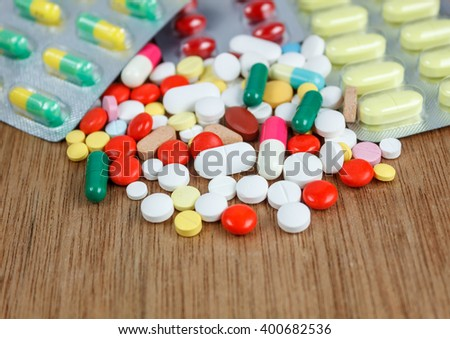 Many colorful medicine,drugs,pill,tablet,capsule,medicine with package on wood background.