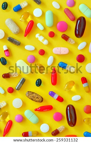 Many colorful pills on yellow background - stock photo