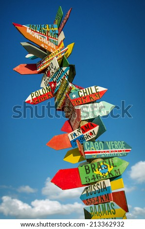 Many colorful wooden direction signs to far locations - stock photo