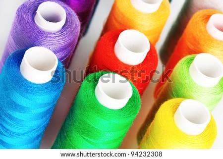 Many-coloured bobbins of thread closeup - stock photo