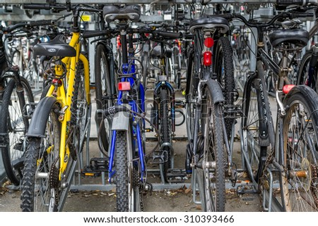 Many commuter bikes parked and locked outside a train station in Chelmsford Essex in August 2015 provide ecological friendly transport for passengers - stock photo