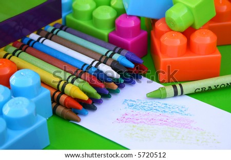 Many crayons and educational toys with some scribbles