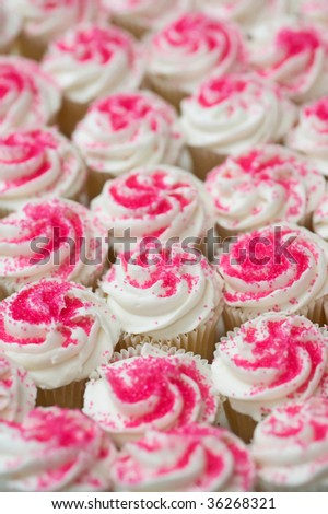 Many cupcakes with white and pink  frosting - stock photo