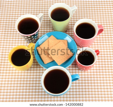 Many cups of coffee on with cookies checkered napkin - stock photo