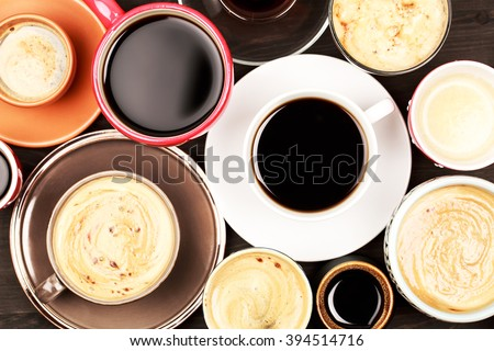 Many cups of coffee on wooden table - stock photo
