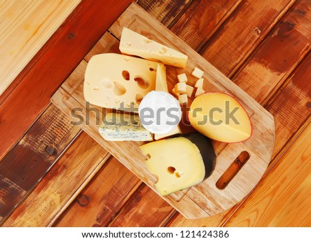 many delicious aged cheeses on wooden plate - stock photo