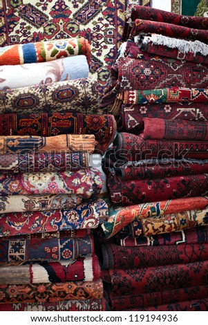 Many different handmade rugs at a flea market