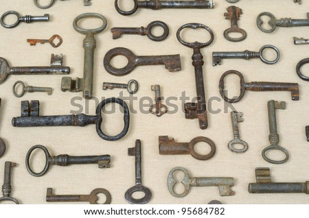 many different old keys on a lighter background fabric - stock photo